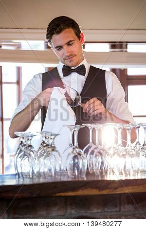 Bartender cleaning wine glass at bar counter
