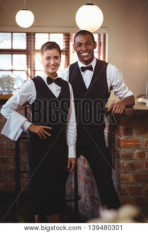 Portrait of smiling waiter and waitress standing together at restaurant