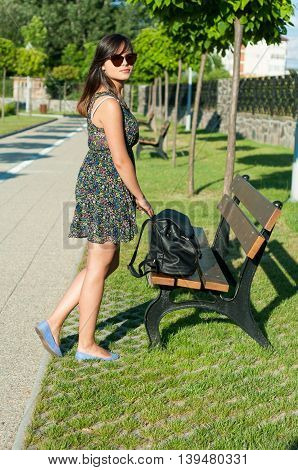 Woman Posing In Park With Backpack On Bench