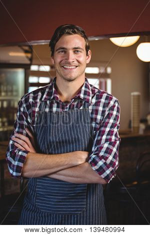 Portrait of smiling waiter standing with arms crossed in restaurant