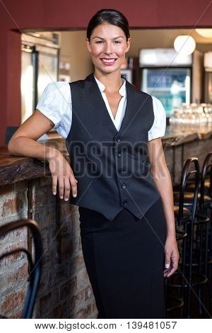 Portrait of smiling waitress standing at bar counter
