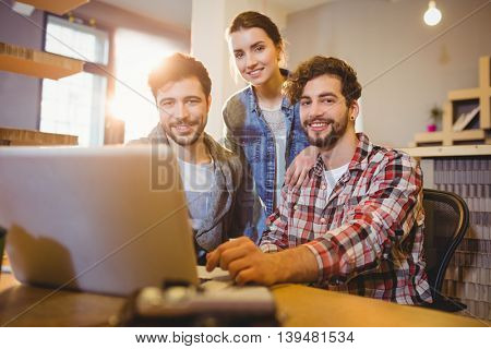 Graphic designer using laptop with his coworker in the office
