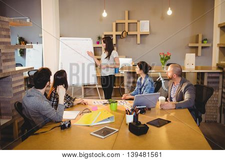 Female graphic designer discussing chart on white board with coworkers in the office