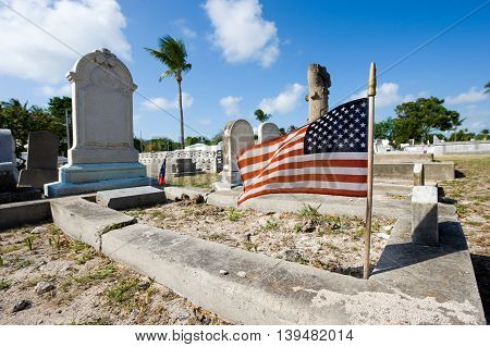 KEY WEST FLORIDA USA - MAY 02 2016: American flag on a grave at the The Key West cemetery. It is a 19-acres cemetery and about 100.000 people are buried here.