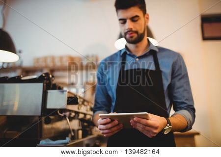 Young man using digital tablet in office cafeteria