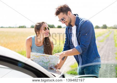 Couple reading a map while standing near convertible
