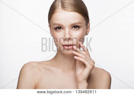 Beautiful young girl with a light natural make-up and French manicure. Beauty face. Picture taken in the studio on a white background.
