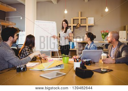 Female graphic designer having discussion with coworkers in the office