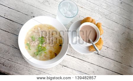 Boiled rice with Minced pork Thai Breakfast have cocoa milk in cup cool water ice and Grilled Chinese Donut at Resort is near the river have sunlight on white wood antique.