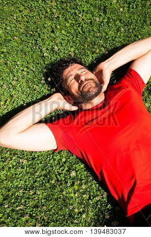 Urban beared athlete happy and smiling resting on the grass is dressed in a  red shirt
