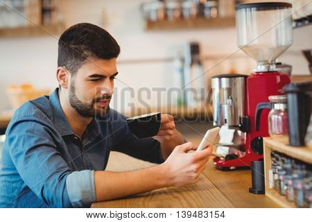 Young man text messaging on mobile phone while having coffee in office cafeteria