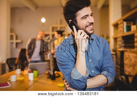 Graphic designer talking on mobile phone while colleagues interacting in background
