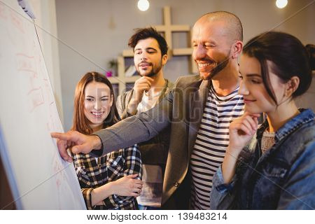 Team of graphic designer discussing chart on white board in the office