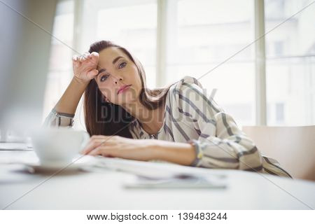 Portrait of thoughtful businesswoman relaxing in creative office