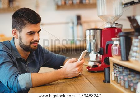 Young man text messaging on mobile phone in office cafeteria