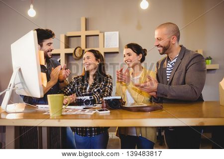 Team of graphic designers applauding a colleague in office
