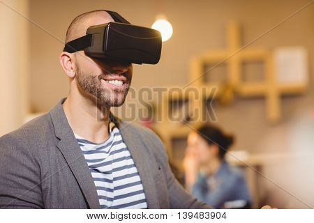 Male graphic designer wearing virtual glasses in office