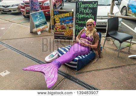 Paihia Bay of Islands New Zealand - November 21 2014: Mermaid girl wearing a mermaid costume on the street of Paihia Bay of Islands New Zealand.