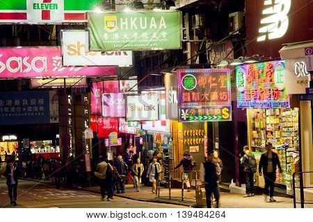 HONG KONG, CHINA - FEB 12, 2016: Night scene with crowd of walking people and billboards of stores and restaurants on February 12 2016. More than 47 million tourists visit Hong Kong annually