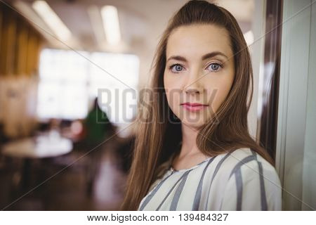 Portrait of young businesswoman in office cafeteria