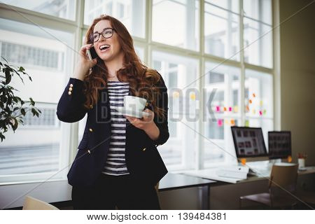 Young businesswoman talking on phone while having coffee in creative office