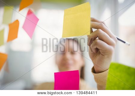 Businesswoman writing on adhesive notes in creative office