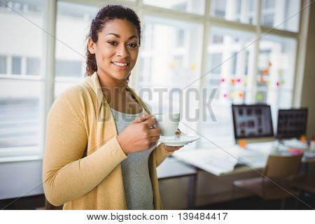 Portrait of young businesswoman having coffee in creative office
