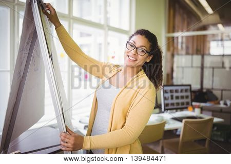 Portrait of young businesswoman giving presentation in creative office