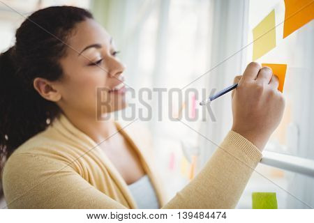 Young businesswoman writing on adhesive notes in creative office
