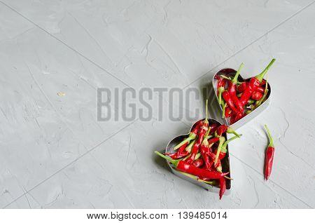 Aluminum heart shapes filled with little chilly peppers on gray background. Concept of hot love and passion
