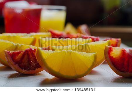 Sliced Sicilian Blood Oranges And Glasses Of Juice On Background