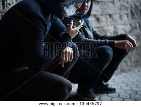 substance abuse, addiction, people and bad habits concept - close up of young men smoking cigarettes outdoors