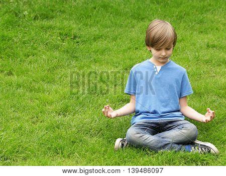cute blond boy sitting on green grass and meditates