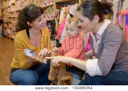 mother friend and daughter in toy store