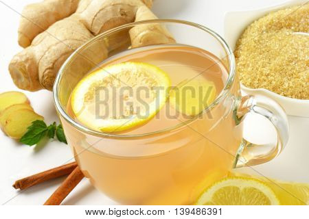 detail of cup of ginger tea with lemon, fresh ginger and cinnamon