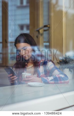 Beautiful young woman using smartphone at cafe