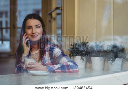 Happy young woman listening to mobile phone at cafe