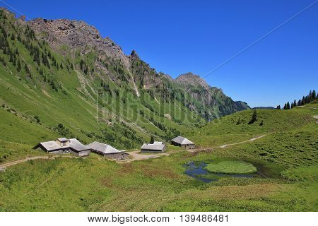 Rural scene in Glarus Canton. Huts and sheds on the Lachenalp. Pond and mountains.