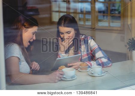 Cheerful young women using digital tablet at coffee shop