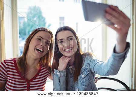 Cheerful young female friends taking selfie at coffee shop