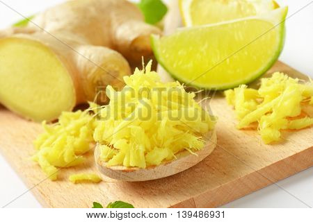 detail of whole and grated fresh ginger with lime on wooden cutting board
