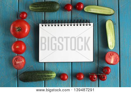 Note book and composition of vegetables on blue wooden desk. Tomatoes, cucumber. Top view.