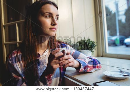 Beautiful young thoughtful woman having coffee at cafe