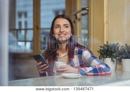 Happy beautiful woman with cellphone and coffee at cafe