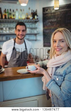 Portrait of beautiful female customer with male barista at cafe