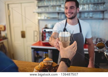 Happy young barista offering coffee in disposable cup to male customer at cafe
