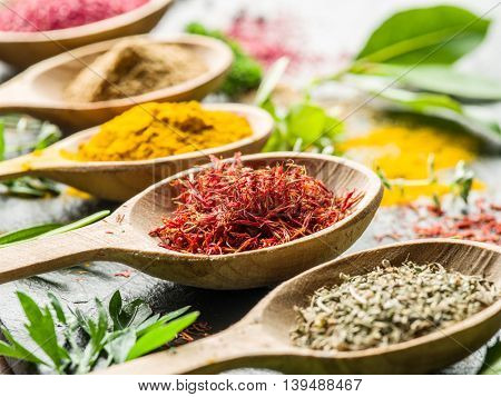 Assortment of colorful spices in the wooden spoons.