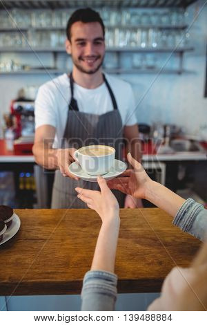 Happy waiter serving coffee to female customer at counter in cafe