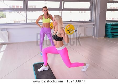 Sporty woman with barbell doing split squat or lunge, instructor monitors the process.