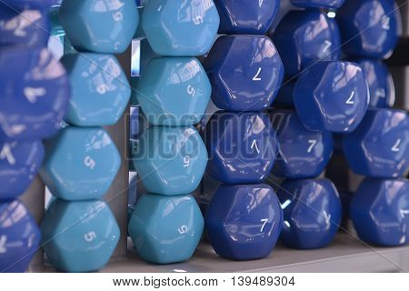 Colored dumbbells of fixed weight in a rack at the gym.
